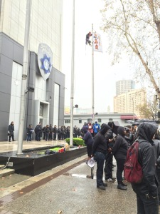 """protester climbs flagpole at Main Entrance to Oakland Police Department headquarters.  Hangs flag w/faces of """"victims."""" Monday, December 15th, 2014"""