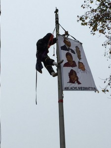 """Demonstrators surround/chain themselves to pole.  Protester climbs flagpole at Main Entrance to Oakland Police Department headquarters.  Hangs flag w/faces of """"victims."""" Monday, December 15th, 2014"""